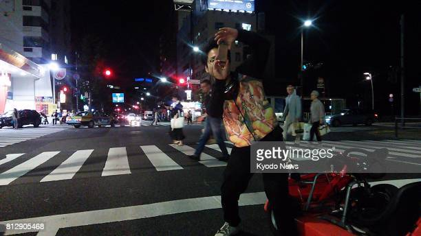A guide and lead driver who works for gokarts operator EcoKart LLC takes photos at an intersection in Roppongi central Tokyo during a twohour gokart...