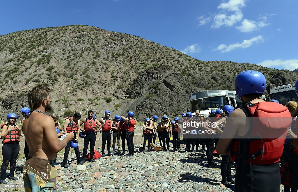 A guide (L) gives instructions to tourists before they go rafting through the rapids in the muddy waters of the Mendoza river near Potrerillos, Argentina on January 29, 2013. AFP PHOTO / DANIEL GARCIA