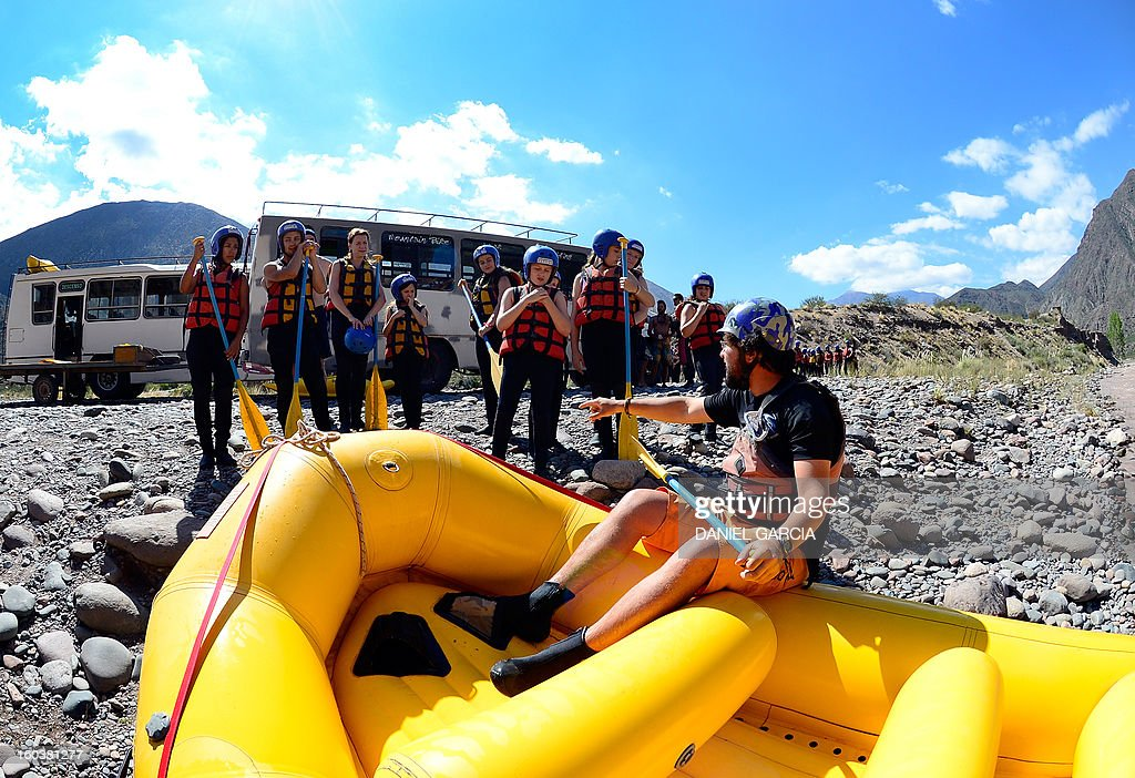 A guide gives instructions to tourists before they go rafting through the rapids in the muddy waters of the Mendoza river near Potrerillos, Argentina on January 29, 2013.
