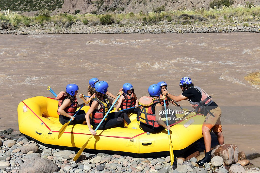 A guide (R) gives instructions to tourists before they go rafting through the rapids in the muddy waters of the Mendoza river near Potrerillos, Argentina on January 29, 2013. AFP PHOTO / DANIEL GARCIA