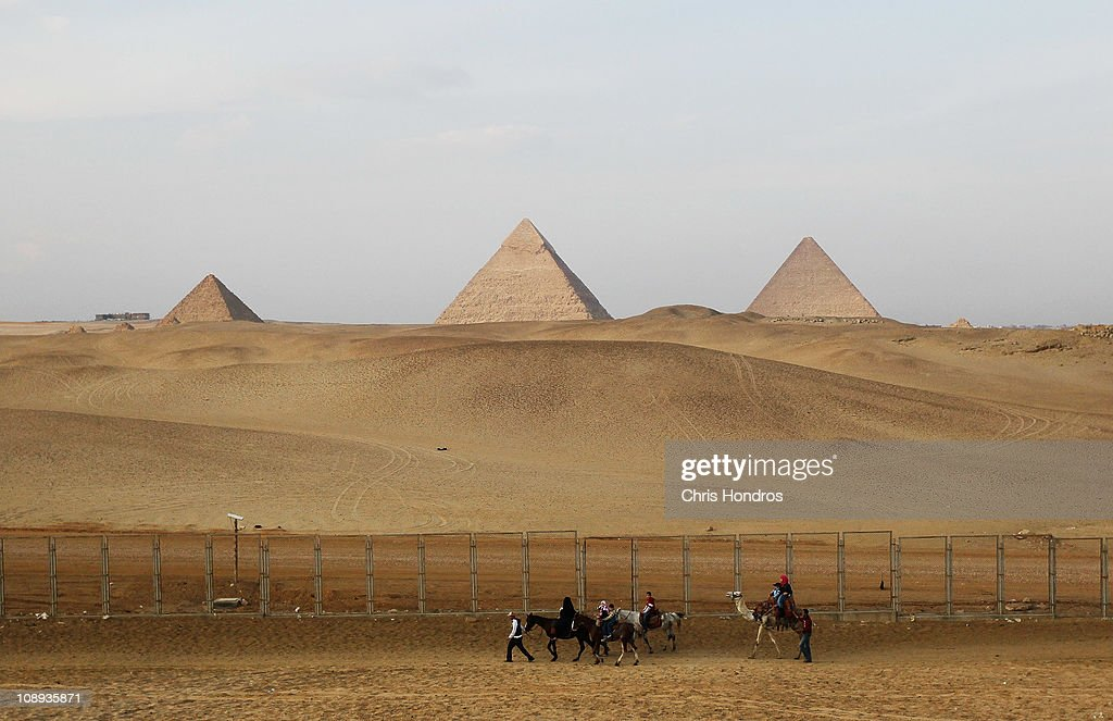 A guide leads Egyptian riders past the Pyramids of Giza Feburary 9, 2011 in Giza, Egypt. Egyptians authorities have re-opened the pyramids to tourists despite massive anti-government protests in nearby Cairo, but foreign visitors are sparse since most tourists fled the country in the wake of the violent clashes.