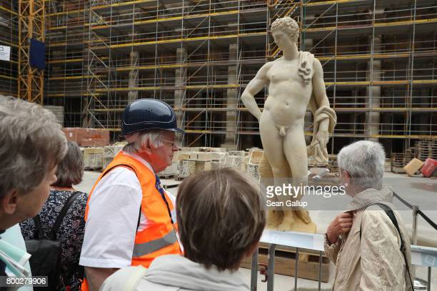 A guide leads visitors to a statue during open house day at the construction site of the Berlin City Palace which will house the Humboldt Forum on...