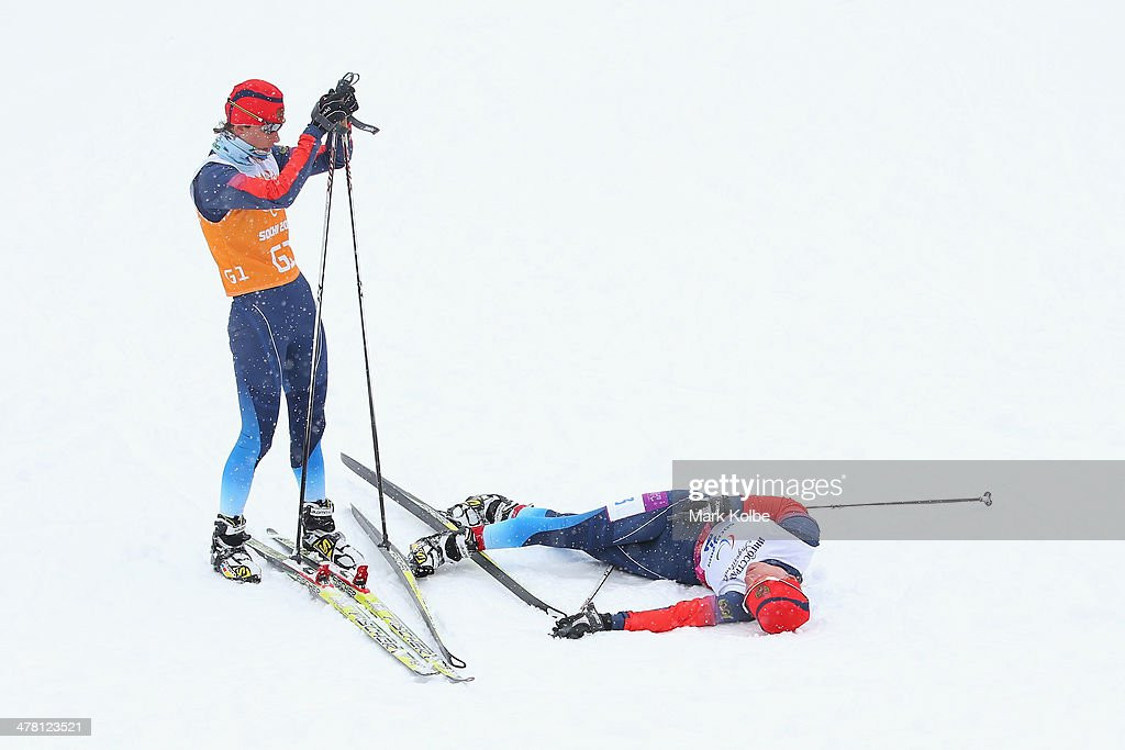 Guide Natalia Yakimova looks on as Elena Remizova of Russia lies on the ground after winning silver in the women's 1km sprint, visually impaired cross-country during day five of Sochi 2014 Paralympic Winter Games at Laura Cross-country Ski & Biathlon Center on March 12, 2014 in Sochi, Russia.