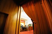A guide of the Great Hall of the People stands behind a curtain at an entrance during the opening session of the Chinese National People's Congress...
