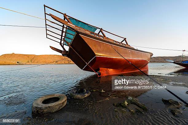 Guide ropes restrain a dhow resting in the mud on a beach at low tide Sur Ash Sharqiyah Region Gulf of Oman Sultanate of Oman