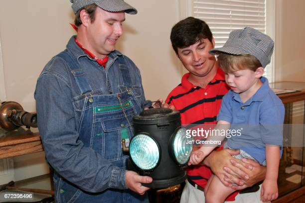 A guide showing a father and son a train lantern in the Tuscumbia Railroad Depot