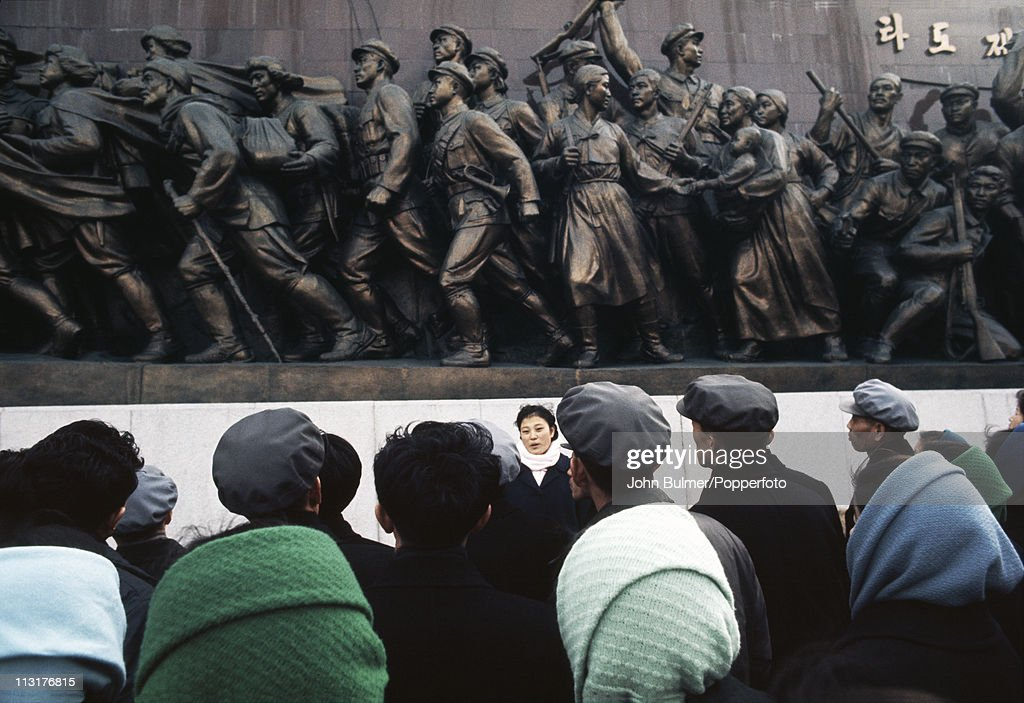 A guide (facing camera) with a group of visitors to the Mansudae Grand Monument, which depicts the North Korean revolutionary struggle, Pyongyang, North Korea, February 1973.
