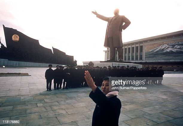 A guide with a group of visitors to the Mansudae Grand Monument which depicts the North Korean revolutionary struggle Pyongyang North Korea February...