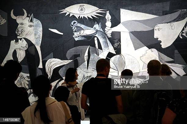 Guide with group of visitors looking at Pablo Picasso's Guernica in Reina Sofia National Art Museum (Museo Nacional de Arte Reina Sofia).