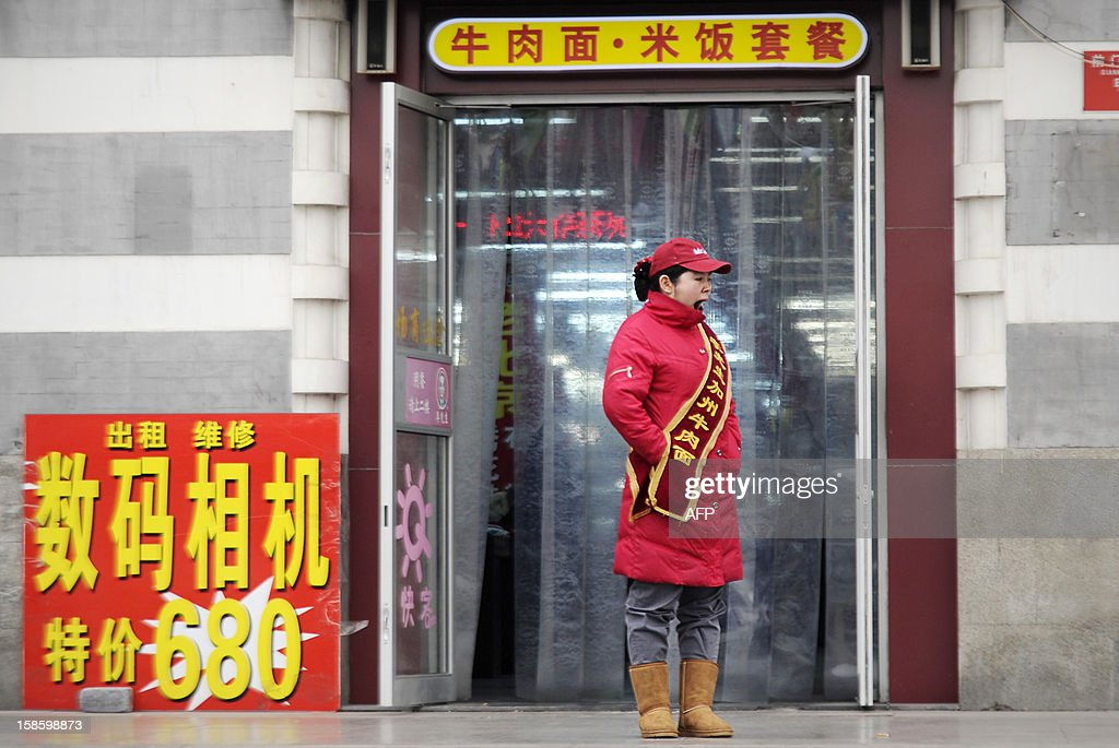A guide yawns at the entrance of a restaurant in Beijing on December 20, 2012. China said on December 18 it faces a bleak foreign trade environment in 2013 due to ongoing global economic weakness, as the Asian export powerhouse appears set to miss this year's trade growth target. AFP PHOTO / WANG ZHAO