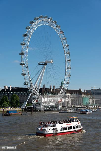 Guided tour boat passing the London Eye on the River Thames London UK