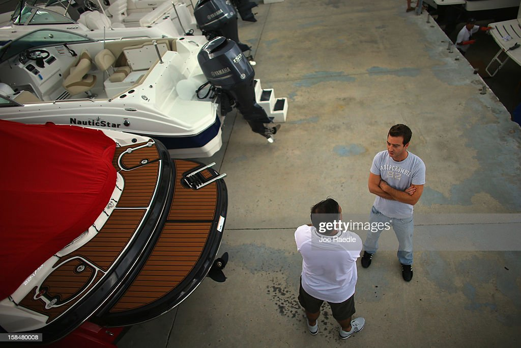 Guido Blanco (L) of Bob Hewes Boats at Arch Creek Marina helps Nicolas Gilberg shop for a powerboat on December 17, 2012 in North Miami, Florida. According to the National Marine Manufacturers Association sales of new recreational powerboats are estimated to be up by 10 percent in 2012.