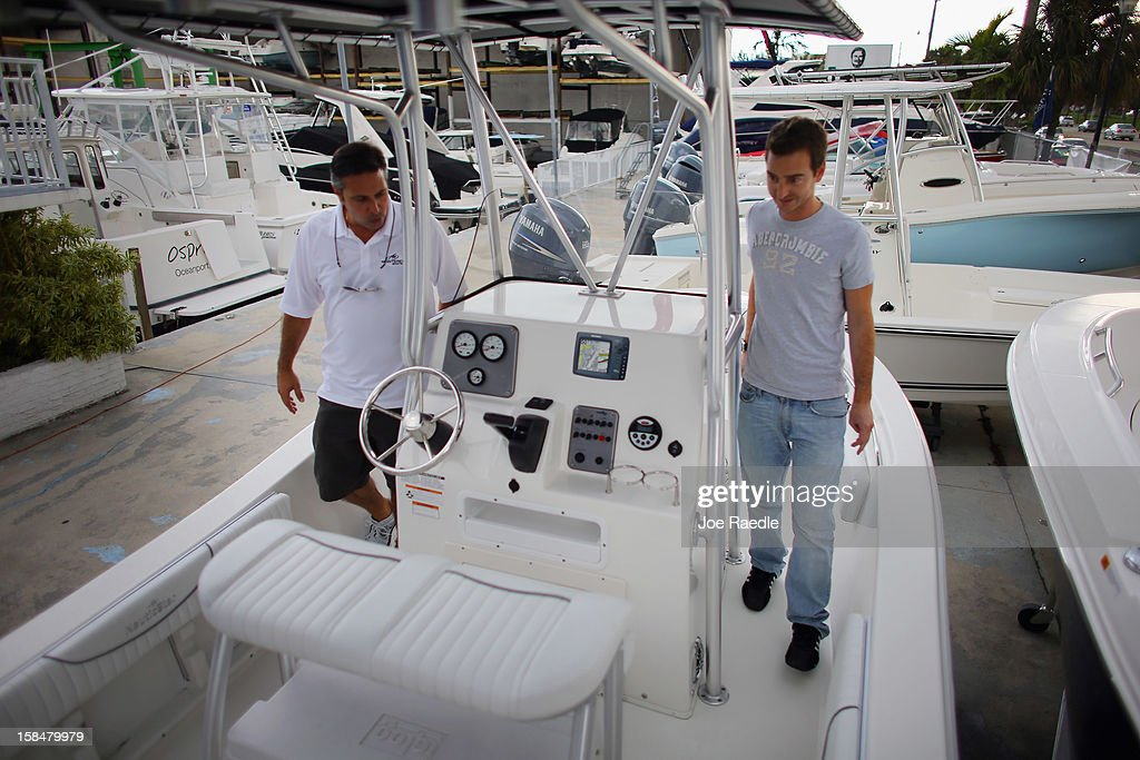 Guido Blanco (L) of Bob Hewes Boats at Arch Creek Marina shows a new boat to Nicolas Gilberg as he shops for a powerboat on December 17, 2012 in North Miami, Florida. According to the National Marine Manufacturers Association sales of new recreational powerboats are estimated to be up by 10 percent in 2012.
