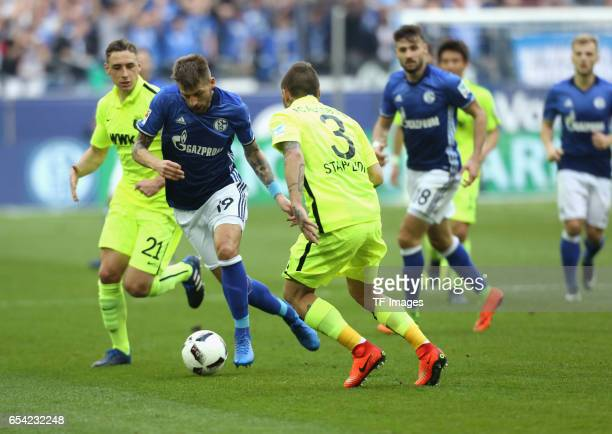 Guido Burgstaller of Schalke and Dominik Kohr of Augsburg and Konstantinos Stafylidis battle for the ball during the Bundesliga match between FC...