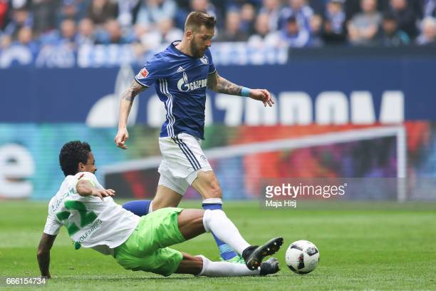Guido Burgstaller of Schalke and Luiz Gustavo of Wolfsburg battle for the ball during the Bundesliga match between FC Schalke 04 and VfL Wolfsburg at...