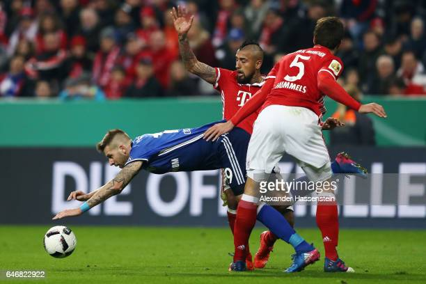 Guido Burgstaller of Schalke is held by Arturo Vidal and Mats Hummels of Muenchen during the DFB Cup quarter final between Bayern Muenchen and FC...