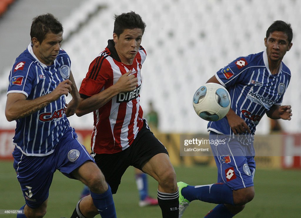 Guido Carrillo of Estudiantes (c) fights for the ball with <a gi-track='captionPersonalityLinkClicked' href=/galleries/search?phrase=Leandro+Grimi&family=editorial&specificpeople=4299733 ng-click='$event.stopPropagation()'>Leandro Grimi</a> (l) during a match between Godoy Cruz and Estudiantes as part of Torneo Inicial at Mundialista Stadium on November 16, 2013 in Mendoza, Argentina.