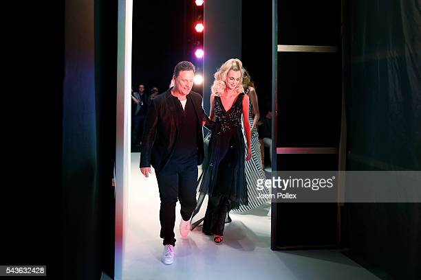 Guido Maria Kretschmer and a model leave the runway after his show during the MercedesBenz Fashion Week Berlin Spring/Summer 2017 at Erika Hess...