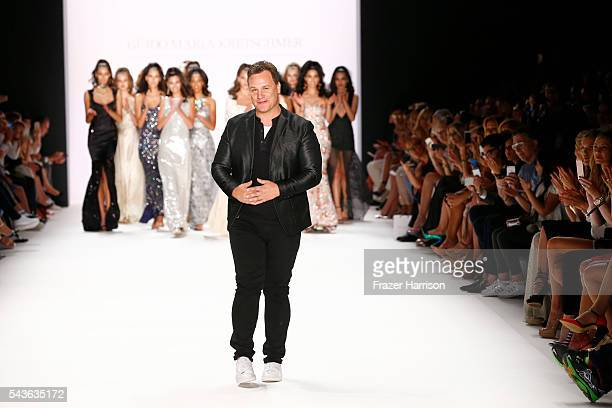 Guido Maria Kretschmer and models acknowledge the applause of the audience at the runway after his show during the MercedesBenz Fashion Week Berlin...