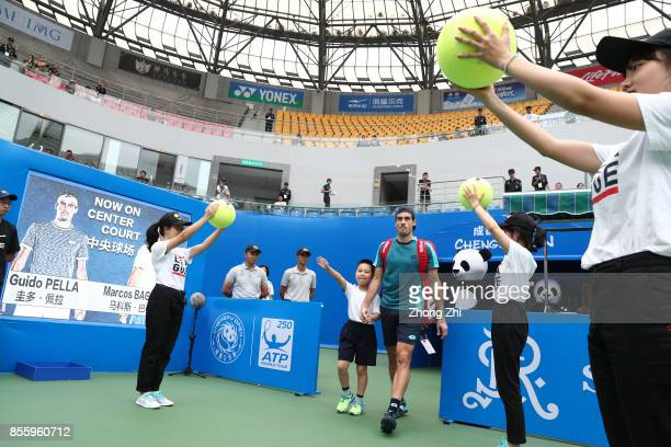 Guido Pella of Argentina enters the court with a kid during the semi final match against Marcos Baghdatis of Cyprus during Day 6 of 2017 ATP Chengdu...