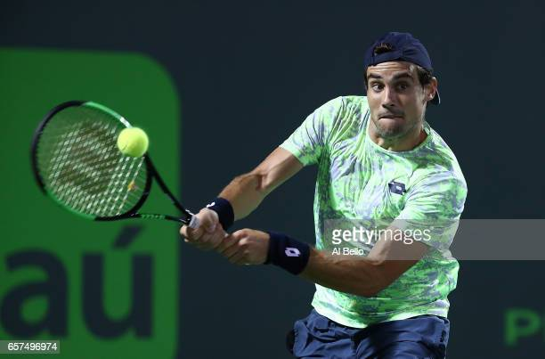 Guido Pella of Argentina returns a shot against Grigor Dimitrov of Bulgaria during day 5 of the Miami Open at Crandon Park Tennis Center on March 24...