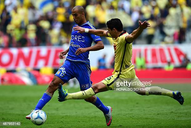 Guido Pizarro of Tigres vies for the ball with Javier Guemez of America during their Mexican Apertura tournament football match at the Azteca stadium...