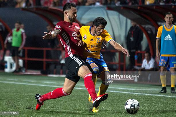 Guido Rodriguez of Tijuana vies for the ball against Damian Alvarez of Tigres during their Mexican Apertura 2016 Tournament football match at...