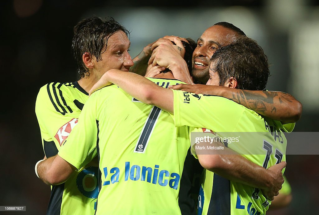 Guilherme Finkler of the Victory celebreates with teammates Archie Thompson, Mark Milligan and Marco Rojas after scoring during the round eight A-League match between the Western Sydney Wanderers and the Melbourne Victory at Parramatta Stadium on November 24, 2012 in Sydney, Australia.