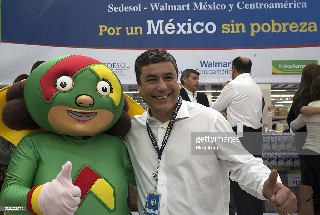 Guilherme Loureiro, chief executive officer of Wal-Mart de Mexico SAB, stands for a photograph with a mascot during an event at a Bodega Aurrera store, the discount chain owned by Wal-Mart Stores Inc., in Naucalpan de Juarez, Mexico, on Wednesday, May 4, 2016. Wal-Mart de Mexico SAB reported first-quarter results last week that beat analysts estimates, the most recent sign of growth for Mexican companies this earnings season. Photographer: Susana Gonzalez/Bloomberg via Getty Images