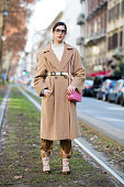Guilia Baggini wears a long tan coat with a belt white turtleneck a pink Valentino studded purse gold silk pajamastyle trousers during the Milan...