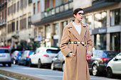 Guilia Baggini wears a long tan coat with a belt white turtleneck and a pink Valentino studded purse during the Milan Men's Fashion Week Fall/Winter...
