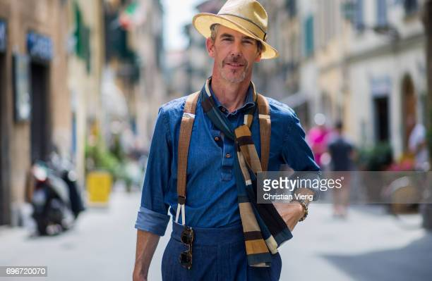 Guillaume Bo wearing denim button shirt and pants straw hat suspenders hand bag is seen during Pitti Immagine Uomo 92 at Fortezza Da Basso on June 16...