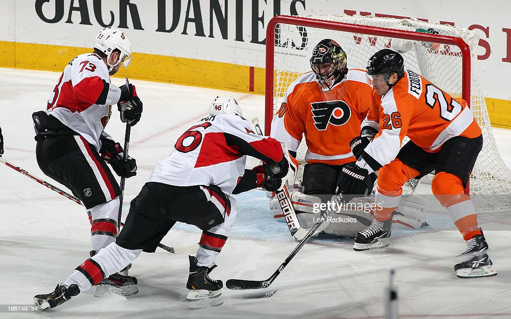 Guillaume Latendresse #73 and Patrick Wiercioch #46 of the Ottawa Senators skate in for a scoring attempt on Ilya Bryzgalov #30 and Ruslan Fedotenko #26 of the Philadelphia Flyers on April 11, 2013 at the Wells Fargo Center in Philadelphia, Pennsylvania.