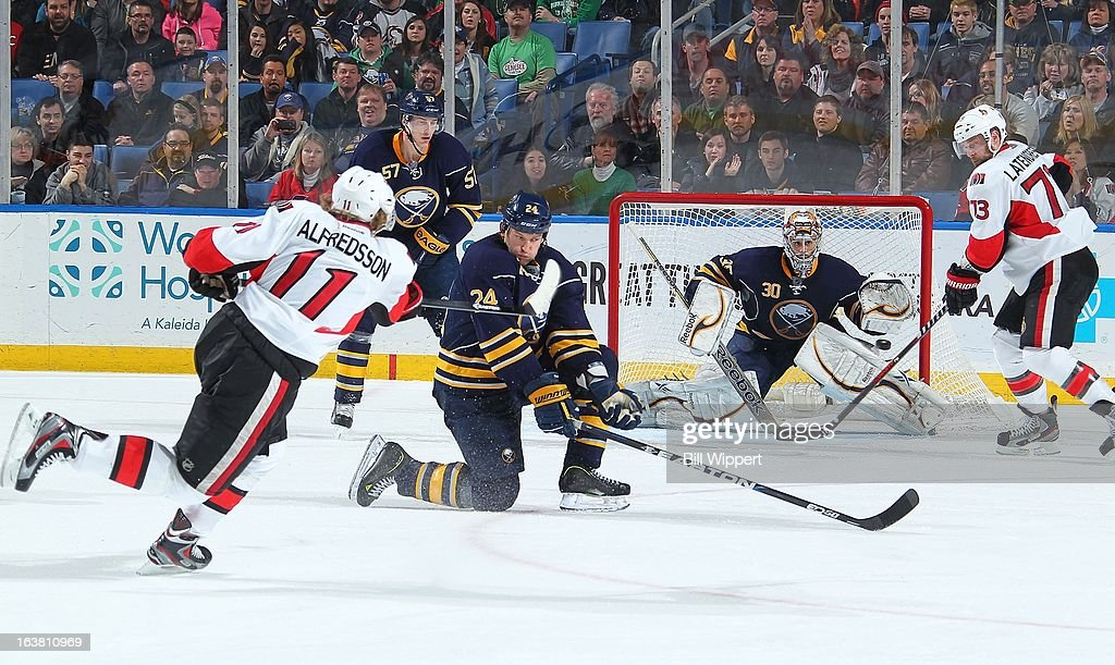 Guillaume Latendresse #73 of the Ottawa Senators looks for a deflection as <a gi-track='captionPersonalityLinkClicked' href=/galleries/search?phrase=Daniel+Alfredsson&family=editorial&specificpeople=201853 ng-click='$event.stopPropagation()'>Daniel Alfredsson</a> #11 shoots the puck past <a gi-track='captionPersonalityLinkClicked' href=/galleries/search?phrase=Robyn+Regehr&family=editorial&specificpeople=171828 ng-click='$event.stopPropagation()'>Robyn Regehr</a> #24 and toward Ryan Miller #30 of the Buffalo Sabres on March 16, 2013 at the First Niagara Center in Buffalo, New York. Ottawa defeated Buffalo, 4-3.