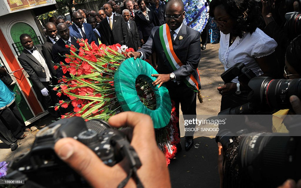 Guillaume Soro (C) president of Ivory Coast National Assembly lays a wreath on January 7, 2013 at the foot of a tree in the Abidjan street where 63 died in a stampede after a firework display, part of the New Year celebrations.