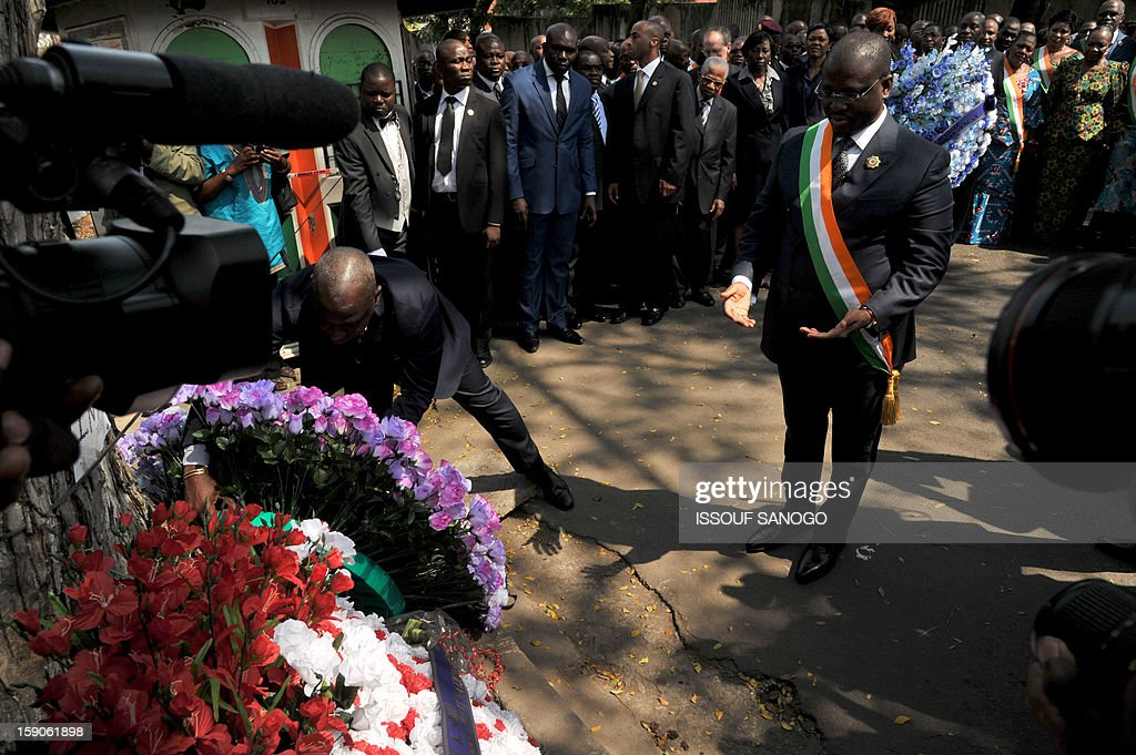 Guillaume Soro (C) president of Ivory Coast National Assembly lays a wreath on January 7, 2013 at the foot of a tree in the Abidjan street where 63 died in a stampede after a firework display, part of the New Year celebrations. AFP PHOTO / ISSOUF SANOGO