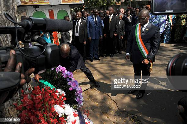Guillaume Soro president of Ivory Coast National Assembly lays a wreath on January 7 2013 at the foot of a tree in the Abidjan street where 63 died...