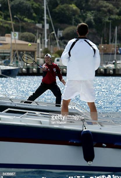 Guillermo Coria of Argentina and Gustavo Kuerten of Brazil play tennis between two boats in Monaco harbour during a photo shoot prior to the ATP...