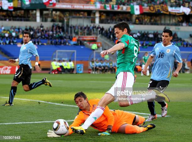 Guillermo Franco of Mexico attempts to round goalkeeper Fernando Muslera of Uruguay during the 2010 FIFA World Cup South Africa Group A match between...