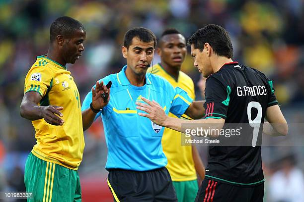 Guillermo Franco of Mexico talks with referee Ravshan Irmatov during the 2010 FIFA World Cup South Africa Group A match between South Africa and...