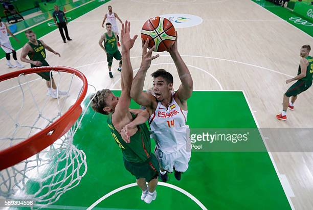 Guillermo Hernangomez Geuer of Spain goes to the basket against Mindaugas Kuzminskas of Lithuania during the Men's Preliminary Round Group B between...