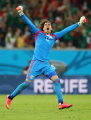Guillermo Ochoa of Mexico celebrates his team's first goal scored by Rafael Marquez during the 2014 FIFA World Cup Brazil Group A match between...