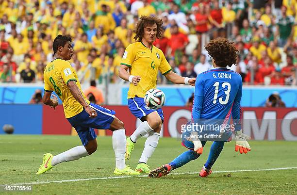 Guillermo Ochoa of Mexico makes a save from Paulinho of Brazil as David Luiz looks on during the 2014 FIFA World Cup Brazil Group A match between...