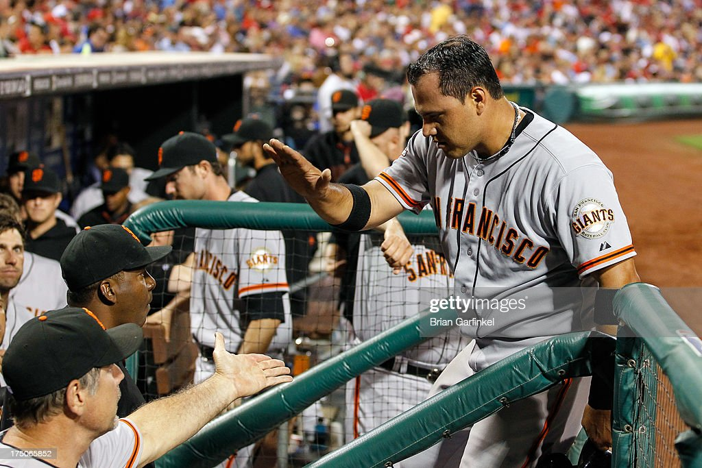 Guillermo Quiroz #12 of the San Francisco Giants is congratulated by teammates after scoring a run in the seventh inning of the game against the Philadelphia Phillies at Citizens Bank Park on July 30, 2013 in Philadelphia, Pennsylvania. The Phillies won 7-3.