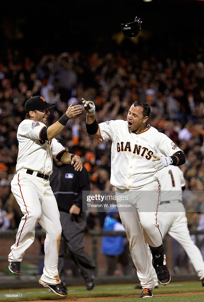 Guillermo Quiroz #12 (R) of the San Francisco Giants on his way to home plate celebrates with <a gi-track='captionPersonalityLinkClicked' href=/galleries/search?phrase=Marco+Scutaro&family=editorial&specificpeople=239523 ng-click='$event.stopPropagation()'>Marco Scutaro</a> #19 (L) after Quiroz hit a walk-off homer against the Los Angeles Dodgers in the bottom of the tenth inning to defeat the Dodgers 10-9 at AT&T Park on May 4, 2013 in San Francisco, California.