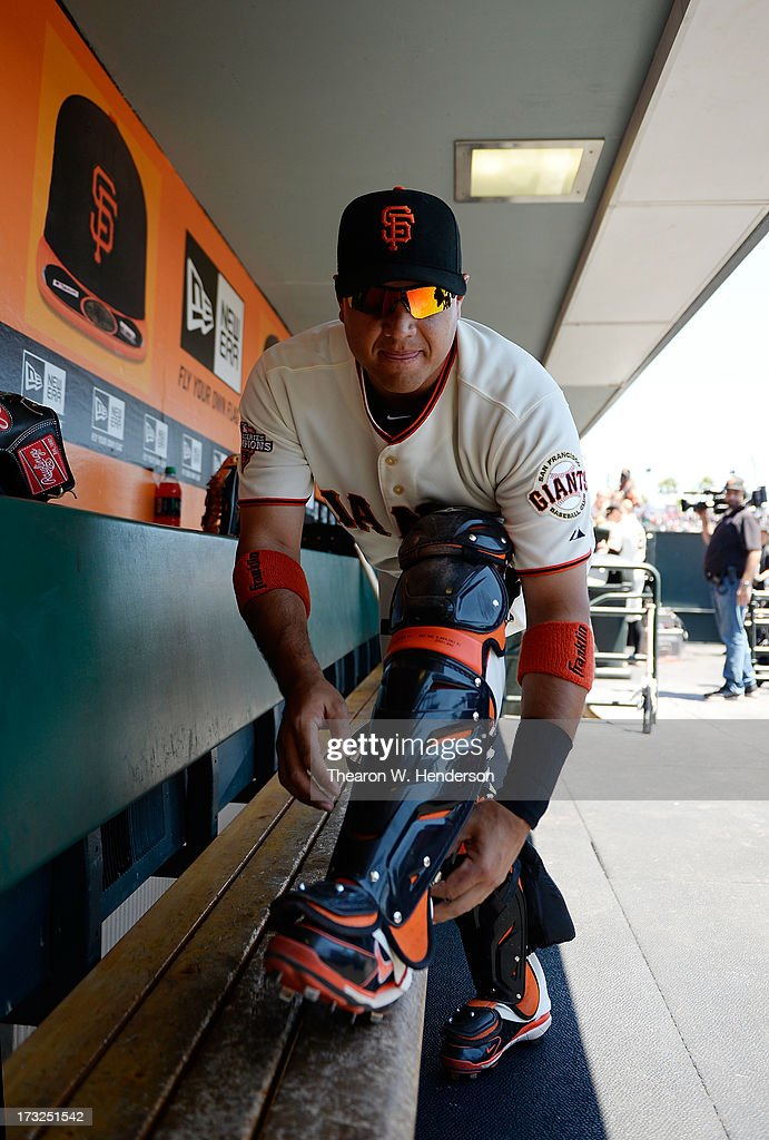 Guillermo Quiroz #12 of the San Francisco Giants puts his catchers gear on in the dugout before the start of their game against the New York Mets at AT&T Park on July 10, 2013 in San Francisco, California.