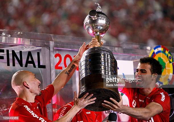 Guinazu and Sandro of Internacional hold the championship trophy after defeating Chivas during a final match as part of the 2010 Copa Santander...