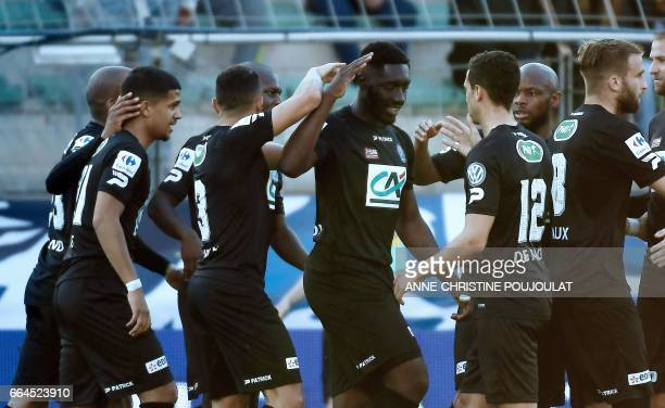 Guincamp's French forward Alexandre Mendy celebrates with teammates after scoring a goal during the French Cup final quarter football match between...