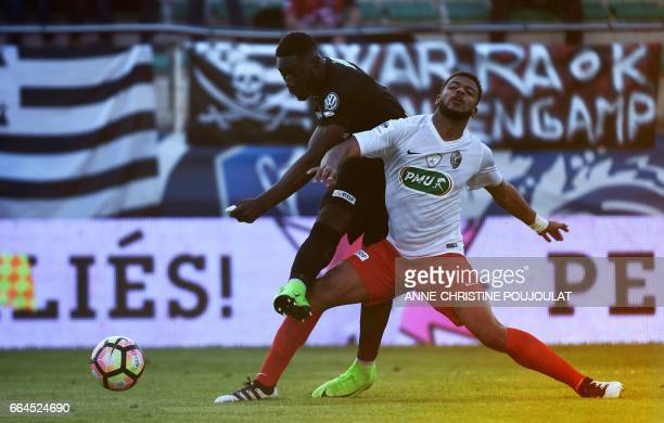 Guincamp's French forward Alexandre Mendy scores in spite of FrejusSaint Raphael's Baissama Sankoh during the French Cup final quarter football match...