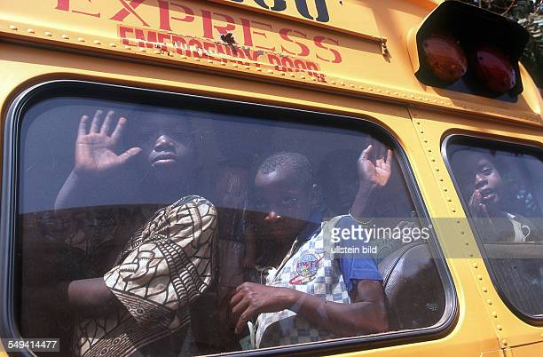 GIN Guinea refugees from Sierra Leone boarding the ferry Fanta to be repatriated Children in a bus on the way to the harbour
